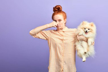 funny girl with stylish striped shirt closing her nose, as the dog is farting