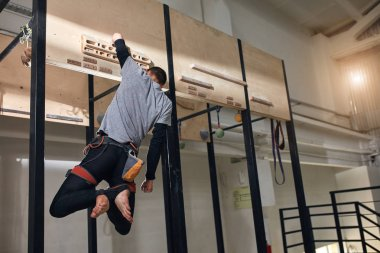 Physically challenged climber performing special exercises at wooden panel