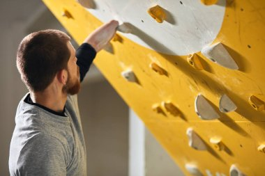 Unrecognizable sportsman without forearm checking holds at climbing wall