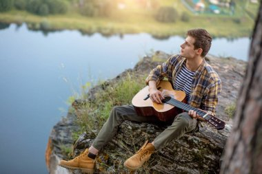 talented creative man playing a guitar on the mountain