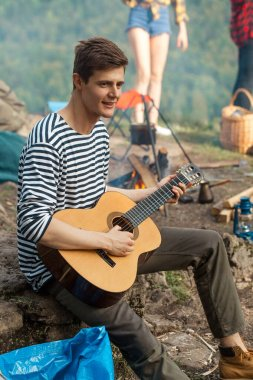 young cheerful handsome talented tourist playing the guitar