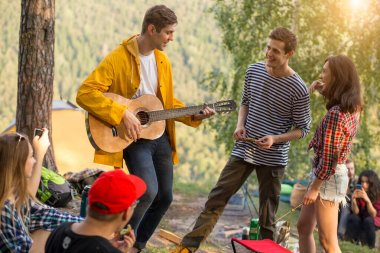 young funny guy performing his song to a friends while resting outdoors