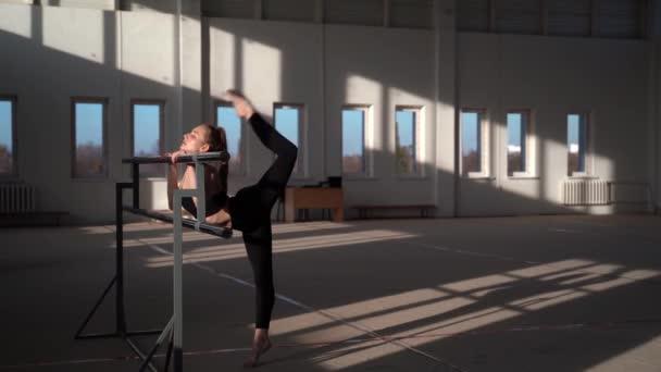 Flexible little girl gymnast doing acrobatic exercise in gym