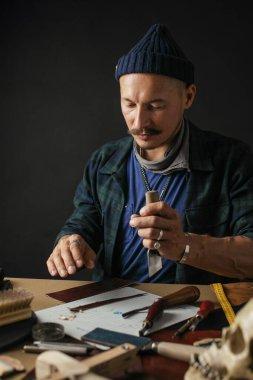 Shoemaker is repairing shoe. Shoemaker sews shoes. Cobbler workshop.