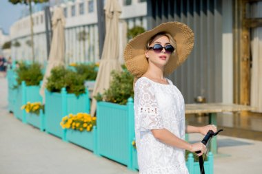 portrait of Trendy woman, beautiful blonde girl in white dress, sunglasses and hat riding scooter