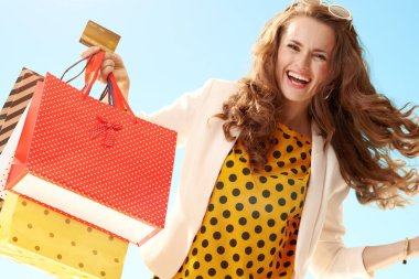smiling modern woman in a light jacket with shopping bags and credit card against blue sky