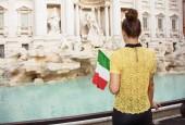 Fotografia vista posteriore di una donna in piedi di camicetta giallo con bandiera italiana vicino a Fontana di Trevi, Roma, Italia