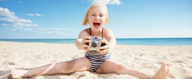 child with opened mouth in swimsuit taking photo with retro film photo camera on seacoast