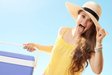 happy woman in straw hat with blue plastic cooler box having fun time and showing tongue out against blue sky