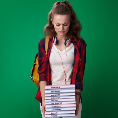 unhappy modern student woman in red shirt with backpack and headphones looking at pile of books in hands on green background