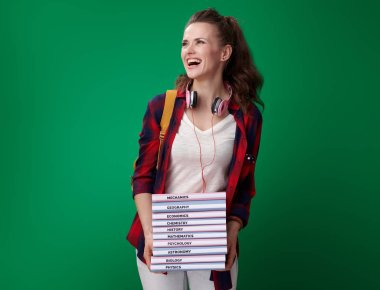 happy modern student woman in red shirt with backpack and headphones holding pile of books and looking aside on green background
