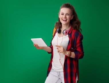 smiling modern student woman in red shirt with backpack and headphones holding tablet PC and pointing aside while posing on green background