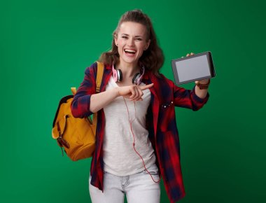 smiling attractive student woman in red shirt with backpack and headphones pointing at tablet PC blank screen on green background