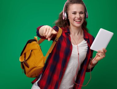 smiling modern student woman in red shirt with backpack and headphones holding tablet PC and pointing at camera against green background