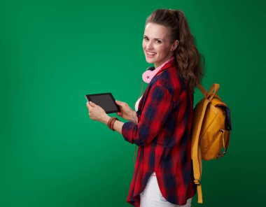 smiling young student woman in red shirt with backpack and headphones using tablet PC and looking at camera on green  background