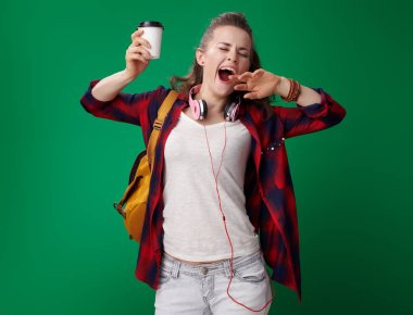young student woman in red shirt with backpack and headphones holding coffee cup and yawing on green background