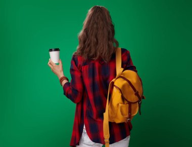 back view of modern student woman in red shirt with backpack and headphones holding coffee cup on green background