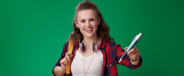 smiling attractive student woman with backpack and headphones showing big pen on green background