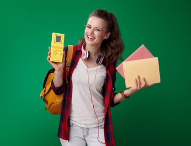 attractive student woman with backpack and headphones choosing between books and video game green background