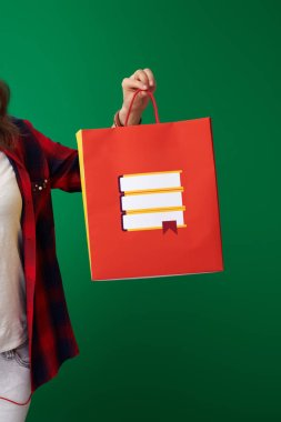 student woman in red shirt with backpack and headphones showing shopping bag with books on green background