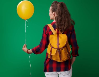 back view of modern student woman in red shirt with backpack and headphones holding yellow balloon on green background