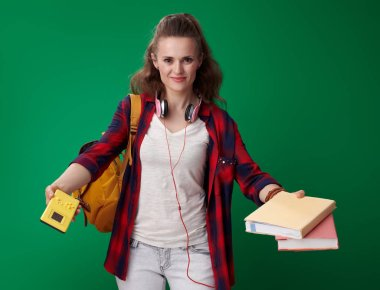 young student woman in red shirt with backpack and headphones holding books and video game on green background