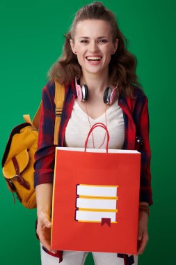 student woman in red shirt with backpack and headphones holding shopping bag with books and laughing while looking at camera on green background