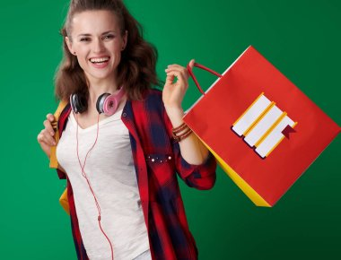 happy young student woman in red shirt with backpack and headphones holding shopping bag with books on green background