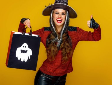 happy modern woman in halloween witch costume showing thumb up and shopping bag on yellow background
