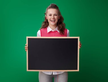 happy modern student woman in a red waistcoat and headphones showing blackboard on green background