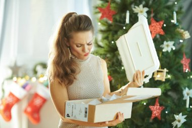 sad modern woman near Christmas tree pulling out broken dish from parcel
