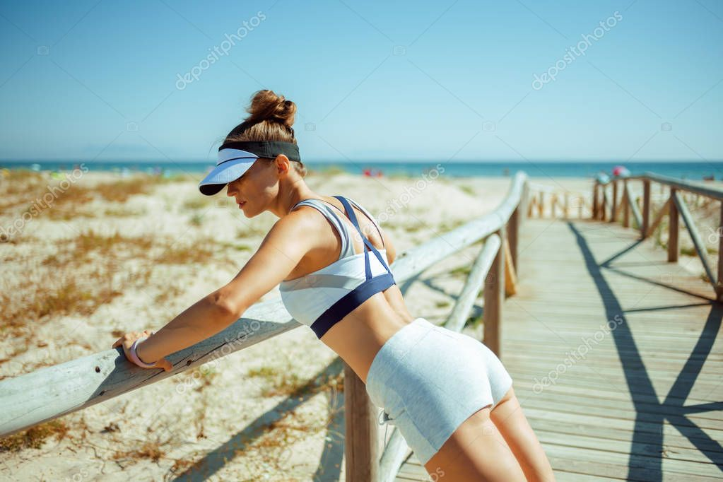 active sports woman in fitness clothes on the ocean coast doing pushups. short bursts of high-intensity exercises to achieve perfect body. 30 something years old woman CEO workout at ocean coast