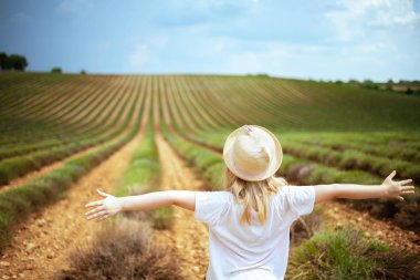 Seen from behind modern child in straw hat in green field in Provence, France rejoicing. green hills. ecotourism. green hills. south France is a region of unique landscape, good cuisine stock vector