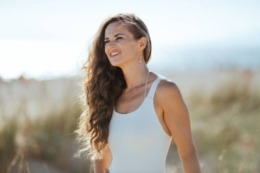 Portrait of smiling modern woman in white swimwear on the seashore looking into the distance. european woman long wavy hair brunette 30 something years old. blue sky. beach vocation.