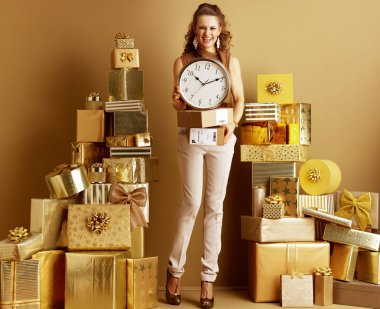 Full length portrait of smiling stylish woman in gold beige pants and brown blouse among 2 piles of golden gifts in front of a plain wall showing parcels and clock. Faster shipments and deliveries.