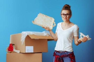 sad modern woman in white t-shirt near cardboard box with a broken dish on blue background