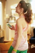 happy woman at modern home updating fitness blog via smartphone