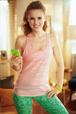 sports woman using online fitness training program in smartphone