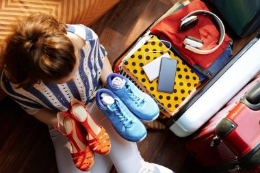 woman packing fashion and comfortable shoes in travel suitcase