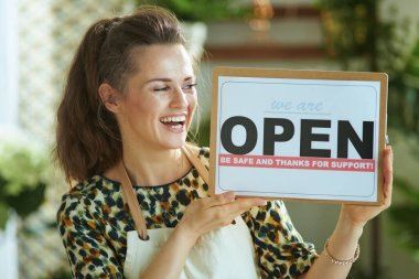 Opening small business after covid-19 pandemic. smiling stylish small business owner woman in apron showing open sign. stock vector