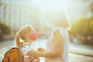 Life during covid-19 pandemic. young mother and school girl with masks and yellow backpack getting ready for school outdoors.