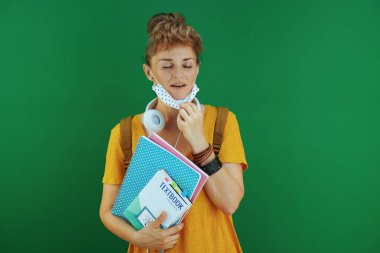 Life during coronavirus pandemic. modern student in yellow shirt with textbooks, notebooks, medical mask, white headphones and backpack breathing against green background.
