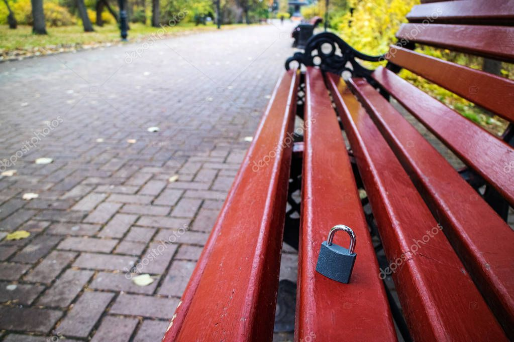 autumn Park with brown benches, fallen leaves and a closed padlock left on the bench