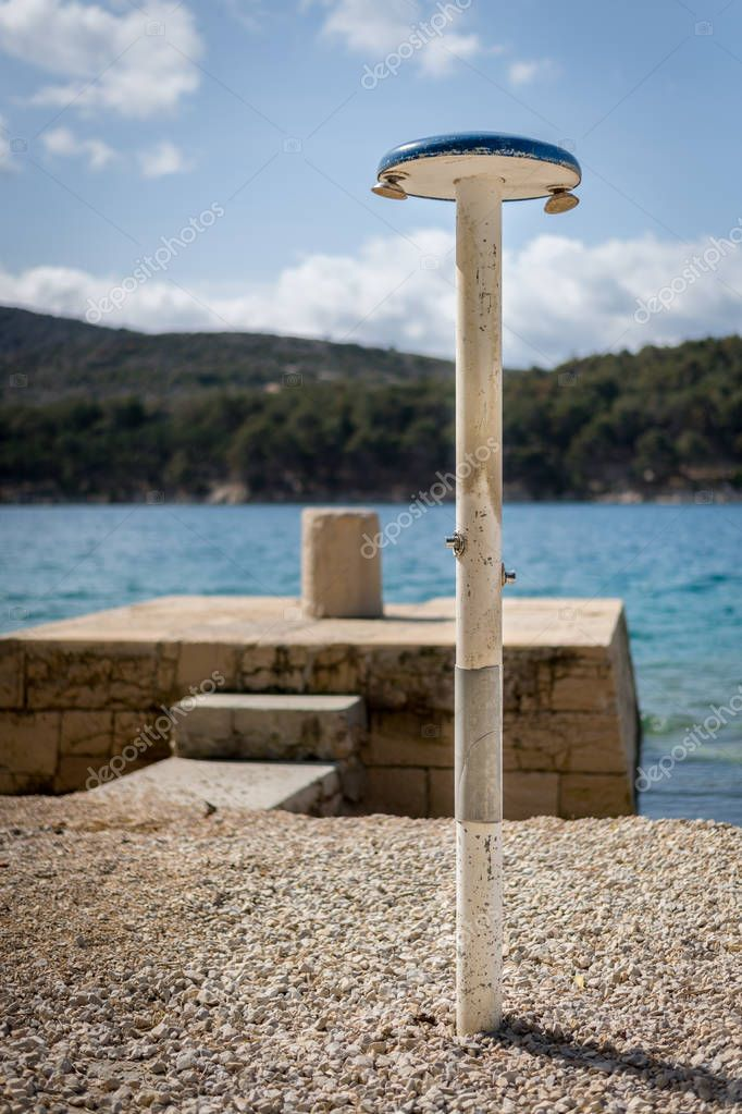 Shower on the beach, berth with bollard in the background, Cres Croatia