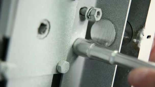 Pracovní tvarové klíče zvratů ořech blokovací mechanismus bezpečné. Zblízka. Jsou viditelné pouze zaměstnance prsty. Zblízka. Veškeré příslušenství a klíče kovové barvy.