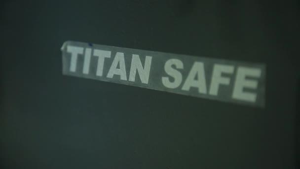 Nápis Titan bezpečný na bezpečné. Zaměstnanec odstraní transparentní ochranný film z nápisem. Neexistuje žádný obličej zaměstnance v záběru. Detailní záběr.