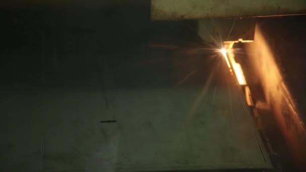 Dělení listů kovu na speciálním stroji. Šlehají jiskry zpod řezací hořák. Zblízka. Proces je automatický