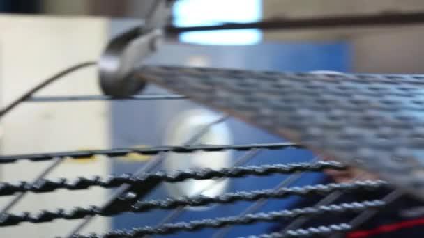Der Mitarbeiter bewegt mit Hilfe des Krans Details für die Montage des Safes. Manipulationen werden im Produktionsraum durchgeführt. Der Haken des Krans und ein Muster von Details sind weithin sichtbar. Details haben charakteristische Metallfarbe.