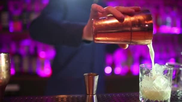 Barmann macht Cocktails mit einem Shaker.