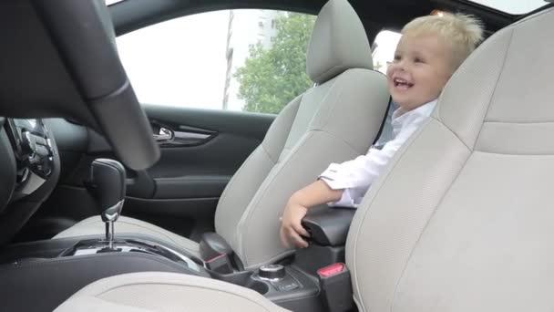 Dítě sedí v salonu vozu na opět sedí. dabbles s loketní opěrkou. tam hází hračky